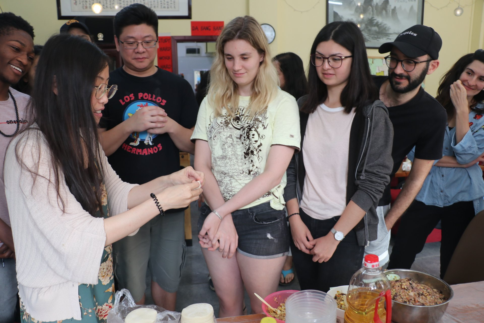 Chinese-teacher-teaching-international-students-how-to-make-dumplings